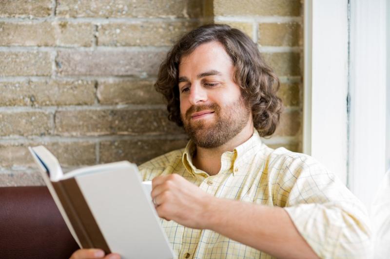 6505789-man-reading-book-in-coffeeshop